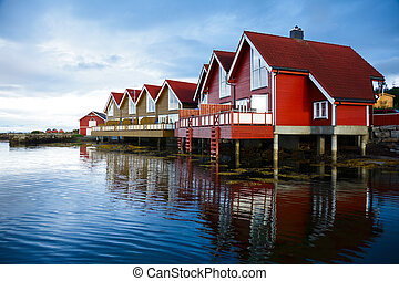 Camping cabins on a fjord - Red wooden cabins at campsite by...