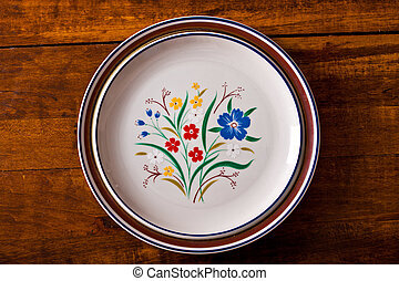 Plates - Top view of a stack of floral plates on a wooden...