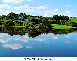 blue sky of Ireland with forests and green meadows and...