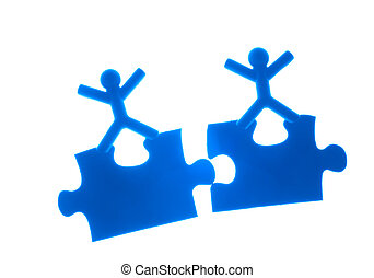 Two people rise hands on top of puzzles