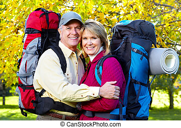Hiking senior couple - Happy senior couple with backpacks in...
