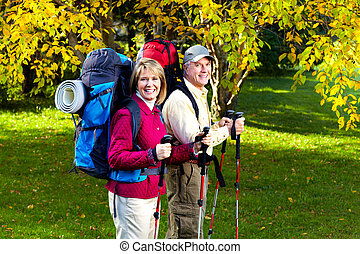 Hiking senior couple - Happy senior couple with backpacks...