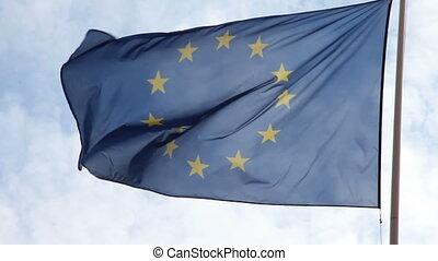 European flag flowing in the wind with a blue sky and white...