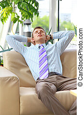 Young relaxed business man with hands behind head at work