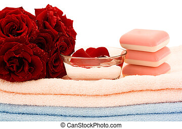 Hygiene - A bouquet of red roses and pink soap on towels