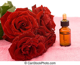 Bath beauty - Bouquet of red roses and rose oil on pink...