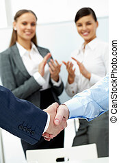 Completing an agreement - Two shaking hands and applauding...