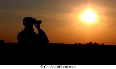binocular 7 - young man looking through binoculars at sunset