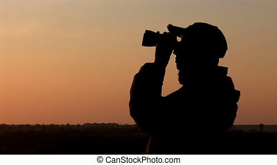 binocular 12 - young man looking through binoculars at...