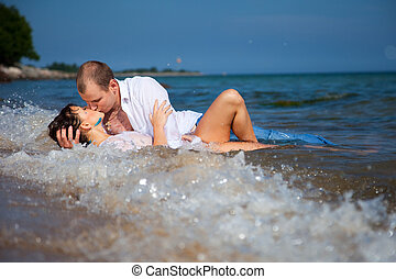 Enamored man and girl kissing in waves of sandy beach