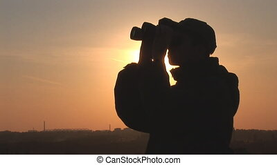 binocular 9 - young man looking through binoculars at sunset