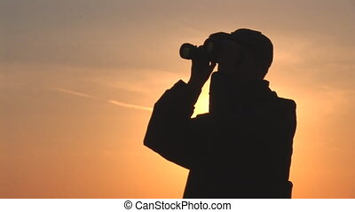 binocular 14 - young man looking through binoculars at...