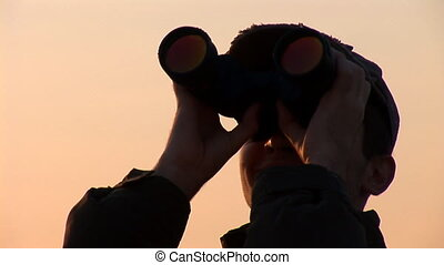 binocular 13 - young man looking through binoculars at...