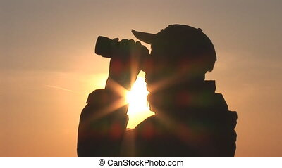 binocular 11 - young man looking through binoculars at...