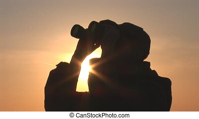 binocular 10 - young man looking through binoculars at...