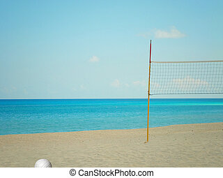 A beach volleyball net and ball on a beach near the...