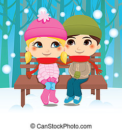 Winter Couple - Young couple sitting on a park bench sharing...