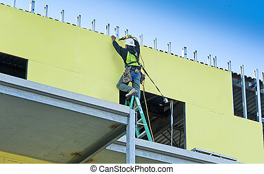 Construction worker screwing outdoor sheet rock into new...