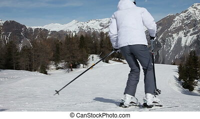 Skiing Downhill - Low angle view of the skiing slope. Woman...