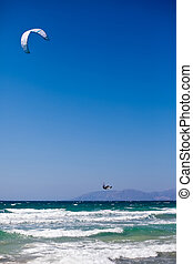 Kitesurfing - unrecognizable man surfing on waves with kite