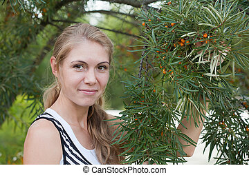 young woman near a bush of sea-buckthorn berries with fruits