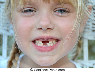 toothy grin - Little blond girl with a toothy grin.