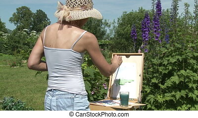 open air   - Young woman painting flowers in the garden