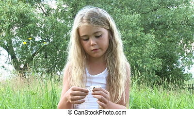 Guessing on a camomile - Little girl guesses on a camomile...