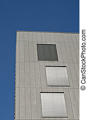 Modern building with metal facade on a blue sky.