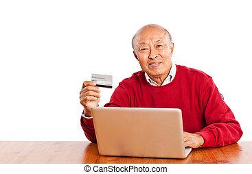 Senior Asian man shopping online celebrating Christmas