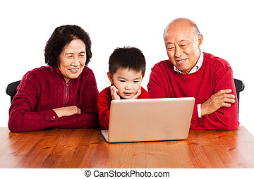 Senior Asian grandparents using computer with their grandson...