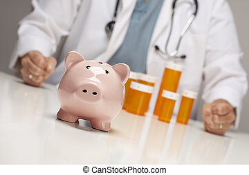 Doctor with Fists on Table Behind Bottle and Piggy Bank -...