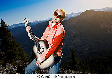 Young woman standing with guitar, against mountain landscape