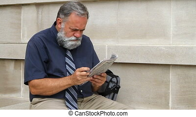 Man Looking For Work - Man sitting by a wall scans the...