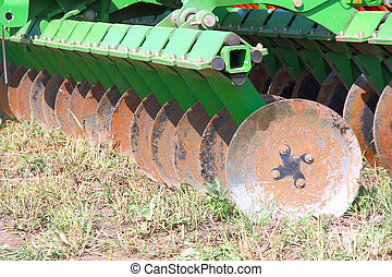 disc harrow behind tractor turning the soil
