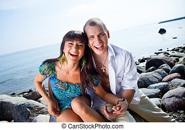 laughing couple near of blue sea