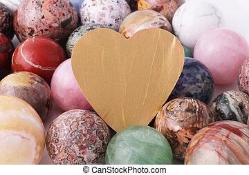 A golden heart with several precious stone balls