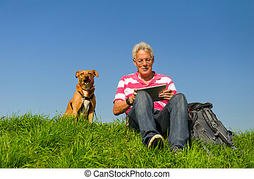 Senior outdoor with tablet PC - Senior man is reading...