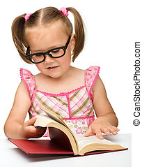 Little girl is flipping over pages of a book - Cute little...