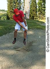 Sand trap - Golfer, using a sand wedge to get his ball out...