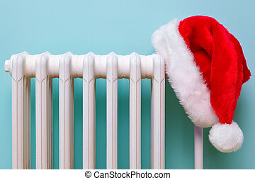 Santa hat on a radiator - Photo of a red and white Father...