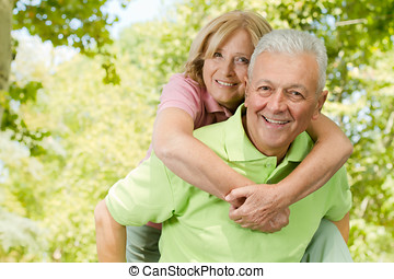 happy senior man giving piggyback ride - Portrait of happy...