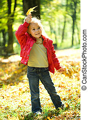 Little girl is playing in autumn park