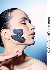 day spa - Portrait of a woman with spa mud mask on her face.