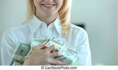 Much money - Happy blonde holding heap of dollar bills in...