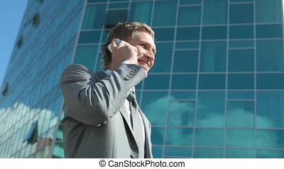Business talk - Businessman talking by cellular phone on...