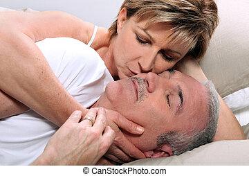 Woman kissing her sleeping husband