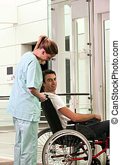 Nurse and patient in wheelchair in front of a lift