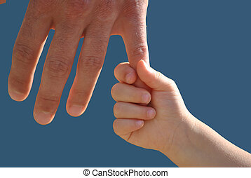 Family hands - A little girl is holding the finger of her...