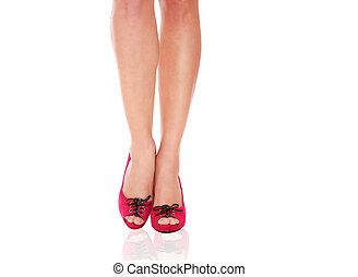 Beautiful female legs wearing red shoes over white...